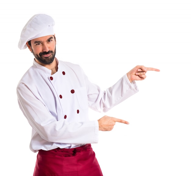 Szef kuchni wskazuj? c na bok na bia? ym tle
