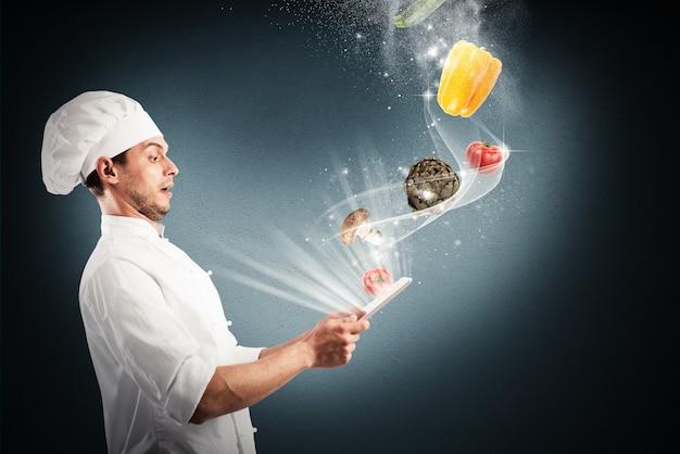 Szef kuchni wygląda na oszołomionego warzywa, które pochodzą z tabletu