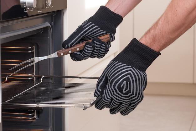 Szef kuchni wyjmuje gorącą blachę z piekarnika w rękawicach ochronnych