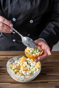 Szef kuchni wypełnia skórkę pomarańczową sałatką