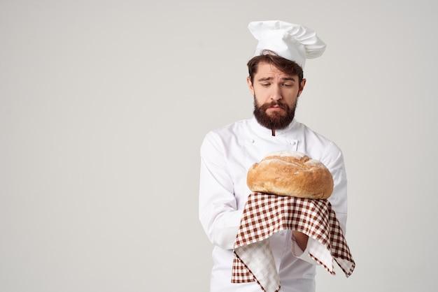 Szef kuchni z chlebem w ręku na białym tle