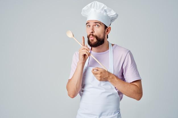Szef kuchni z drewnianą łyżką w rękach profesjonalnej obsługi restauracji