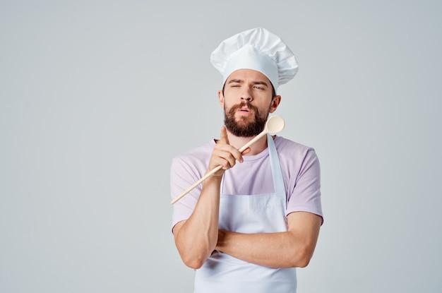 Szef kuchni z drewnianą łyżką w ręku pracujący profesjonalista w kuchni