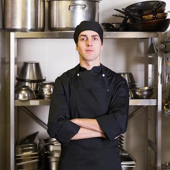 Szef kuchni z kuchnią mundurową i kuchenną