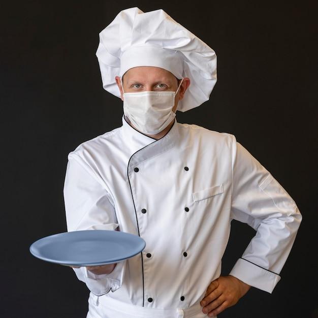 Szef kuchni z maską medyczną trzymając talerz