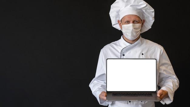 Szef kuchni z medyczną maską trzymając laptopa