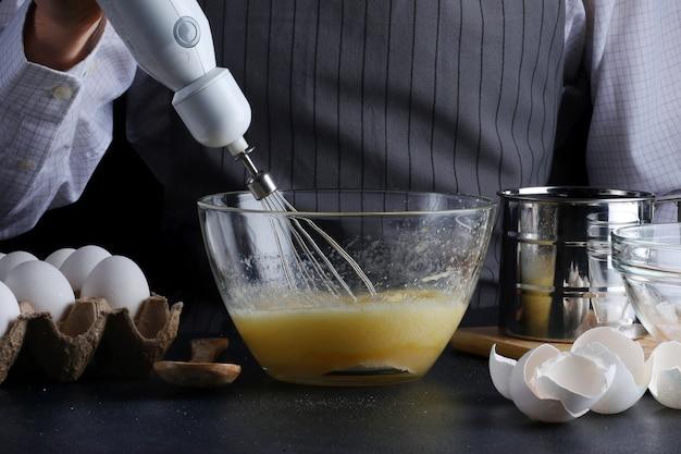 Szef kuchni z mikserem w rękach gotowanie ciasta ze składnikami na stole