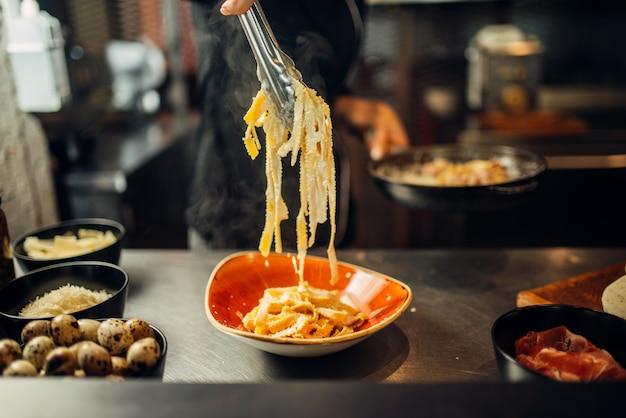 Szef kuchni z patelni gotowania makaronu na drewnianym stole. dekorowanie na stek, przygotowanie potraw w kuchni