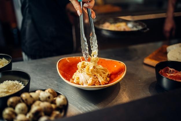 Szef kuchni z patelni gotowania makaronu na drewnianym stole