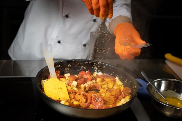 Szef kuchni z rękawiczkami w rękach dodaje przyprawy do patelni z naczyniem do gotowania