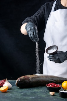 Szef kuchni z widokiem z przodu w białym fartuchu posypany solą na świeżych nasionach granatu ryb w misce na stole
