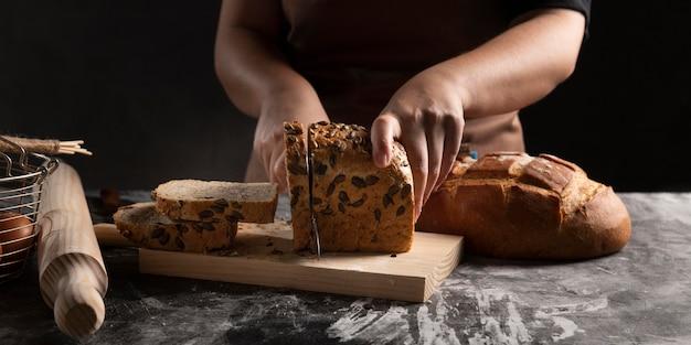 Szef kuchni za pomocą noża kroi chleb na desce do krojenia