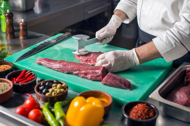 Szef kuchni zmiękcza stek z zmiękczaczem mięsa na desce do krojenia