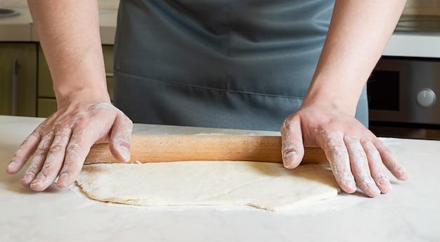Szef kuchni zwija ciasto drewnianym wałkiem do ciasta