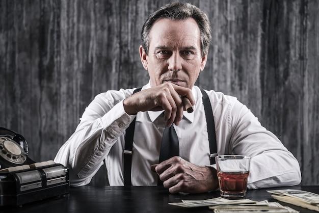 Szef mafii. poważny starszy mężczyzna w koszuli i szelkach siedzi przy stole i pali cygaro, podczas gdy obok niego leży mnóstwo pieniędzy