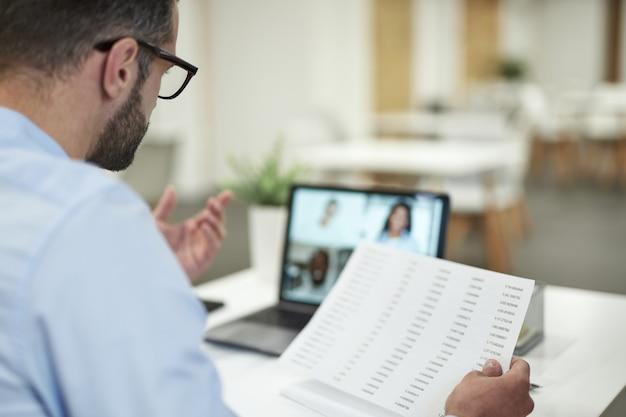 Szef mający spotkanie online i trzymający dokumenty