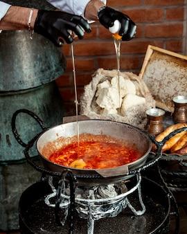 Szef nalewa jajka do omletu pomidorowego