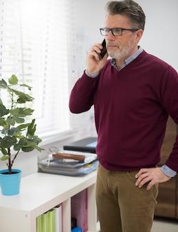 Szef rozmawia przez telefon obok okna