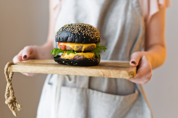 Szef trzyma drewnianą deskę do krojenia z czarnym burgerem.