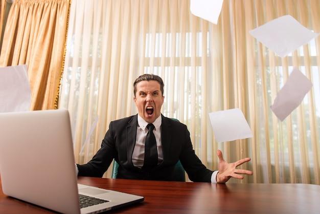 Szef w garniturze rzuca papierami i krzyczy w pomieszczeniu