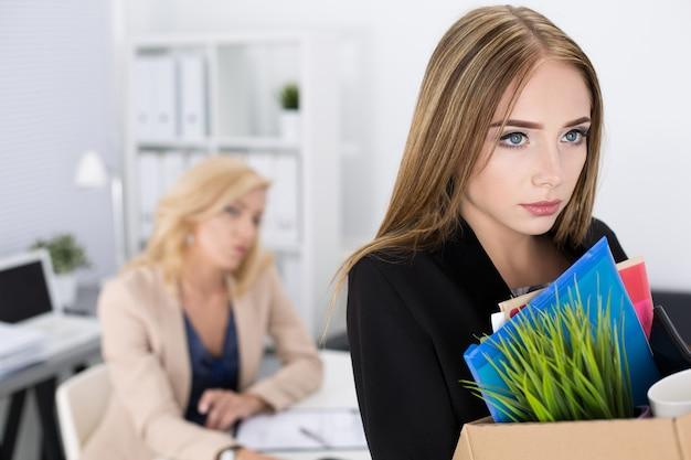 Szef zwalniający pracownika. przygnębiony zwolniony pracownik biurowy niosący pudełko pełne rzeczy. wywalanie koncepcji.