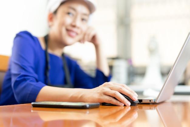 Szefa kuchni bizneswoman ono uśmiecha się przy kamerą podczas gdy pracujący na laptopie w domu.