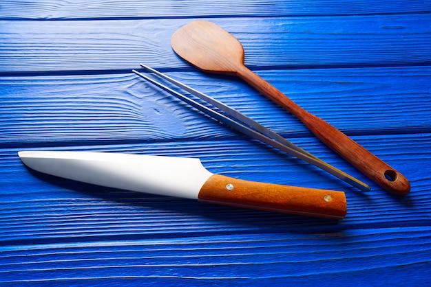 Szefa kuchni narzędzia na błękitnym drewnianym tle