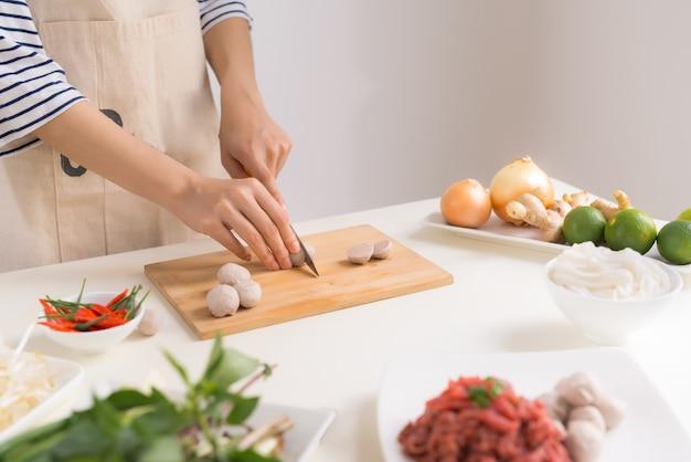 Szefowa kuchni przygotowuje tradycyjną wietnamską zupę pho bo z ziołami, mięsem, makaronem ryżowym