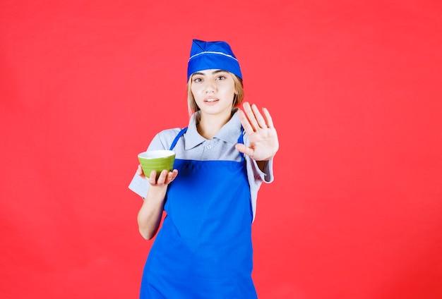 Szefowa kuchni w niebieskim fartuchu trzyma kubek z zielonym makaronem i zatrzymuje kogoś