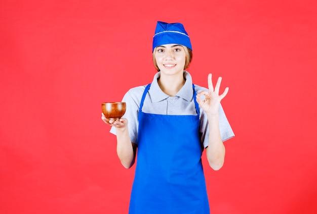 Szefowa kuchni w niebieskim fartuchu trzymająca filiżankę chińskiej miedzi i pozytywnie nastawiona do smaku