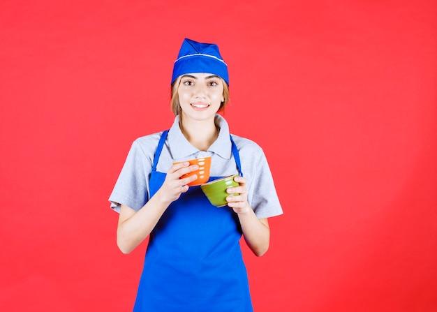 Szefowa kuchni w niebieskim fartuchu, trzymająca pomarańczowe i zielone ceramiczne kubki z makaronem