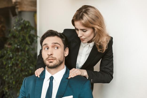Szefowa uwodzi pracownika. młoda dziewczyna trzyma za ramiona kolegi, który siedzi przy stole. patrzy na nią zdziwiony.