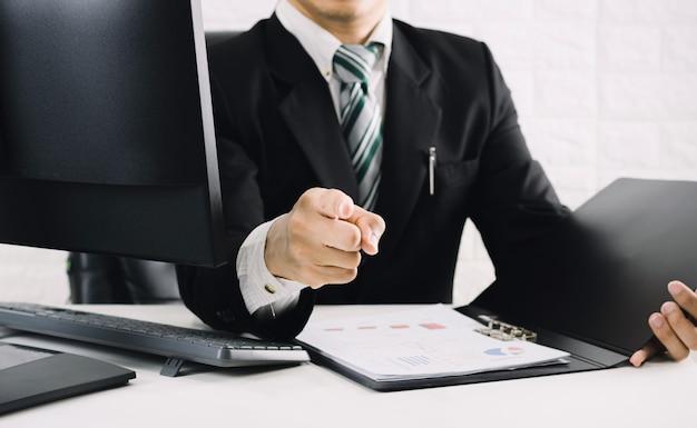 Szefowie biznesmenów wskazując palcem na biurko