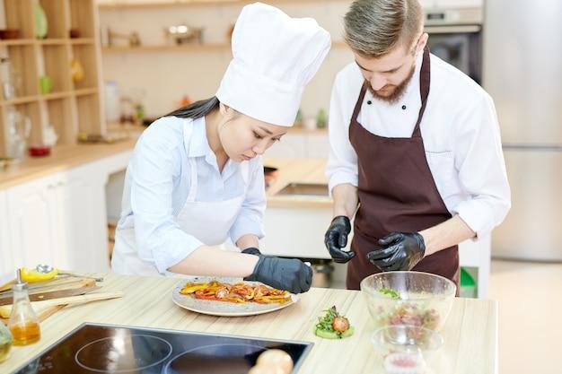 Szefowie kuchni pracujący nad potrawami