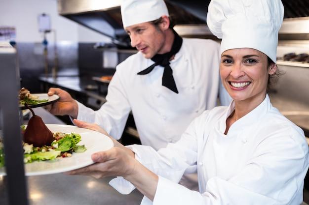 Szefowie kuchni przekazują talerze obiadowe przez stację zamówień