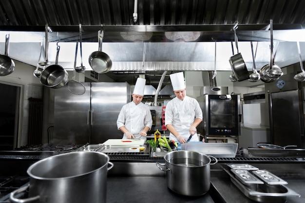 Szefowie kuchni przygotowują posiłki w kuchni