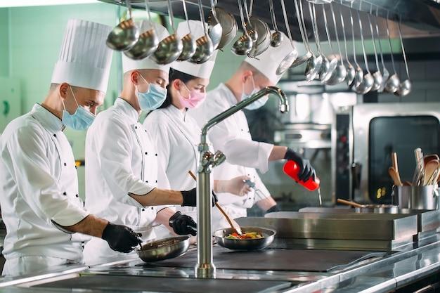 Szefowie kuchni w maskach ochronnych i rękawiczkach przygotowują jedzenie w kuchni restauracji lub hotelu.