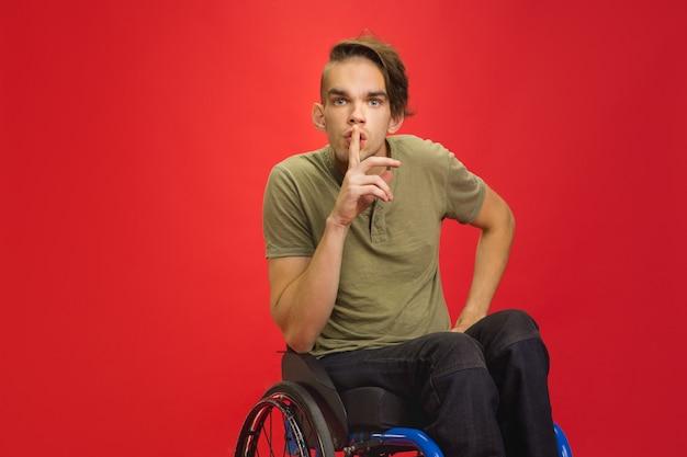 Szepczące sekrety portret młodego niepełnosprawnego mężczyzny rasy kaukaskiej na czerwonej ścianie studia
