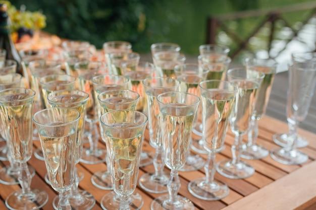 Szereg kieliszków wypełnionych szampanem są ustawione w kolejce, gotowe do podania