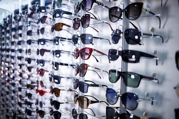 Szereg okularów chroniących przed słońcem. przechowuj punkty. stań z okularami przeciwsłonecznymi w sklepie optycznym. ręka pokazuje okulary. prezentacja punktów. zbliżenie