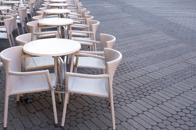 Szereg pustych stołów z krzesłami jest połączonych kablem z kradzieży w kawiarni na ulicy.