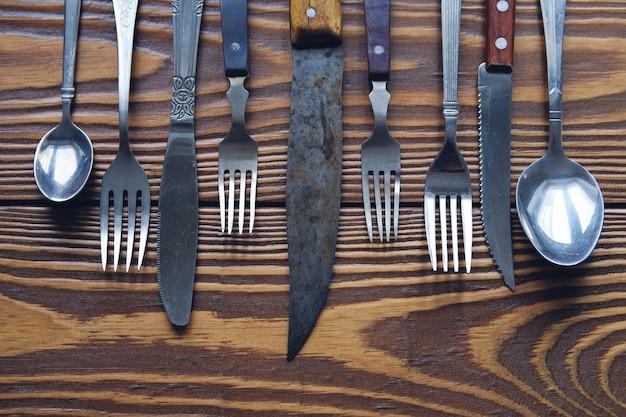 Szereg różnych zabytkowych sztućców z nożami, widelcami i łyżkami.