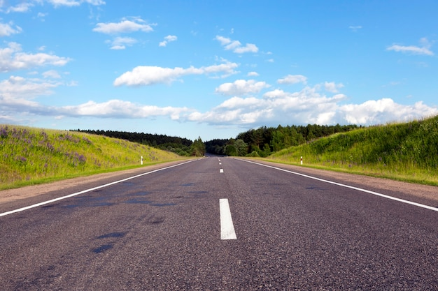 Szeroka asfaltowa droga biegnąca przez las porośnięty różnymi drzewami, słoneczna pogoda i błękitne niebo