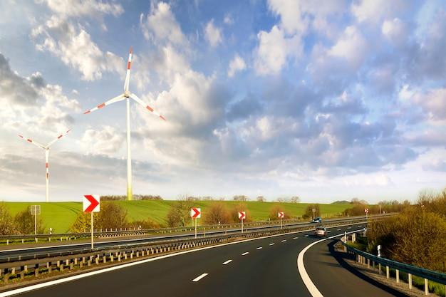Szeroka autostrada z jadącym samochodem sięgającym horyzontu przez zielone wzgórza