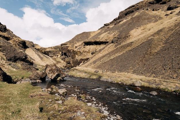 Szeroka górska rzeka wśród gór w islandii na tle błękitnego nieba z chmurami