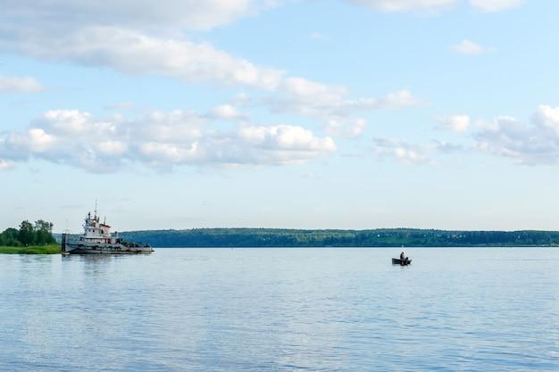 Szeroka letnia rzeka z łodzią rybacką i holownikiem przy brzegu