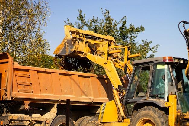 Szeroka metalowa łyżka koparki wykopuje piasek lub glinę i ładuje ją do wywrotki na placu budowy.