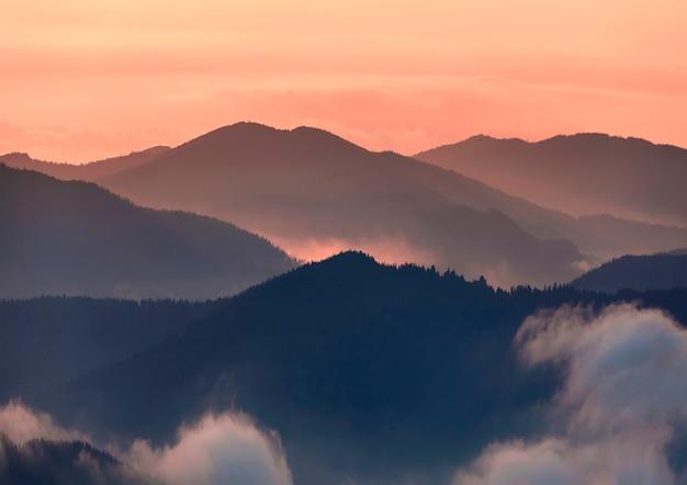 Szeroka panorama, fantastyczny widok pokrytych poranną mgłą zielonych karpat o zachodzie słońca na jasnym jasnym pomarańczowym niebie. piękno przyrody, turystyki i koncepcji podróży.
