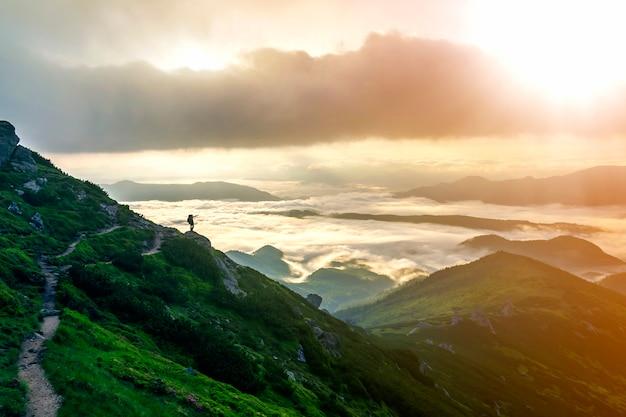 Szeroka panorama górska. mała sylwetka turysty z plecakiem na skalistym zboczu góry wskazującym na dolinę pokrytą gęstymi białymi bufiastymi chmurami.