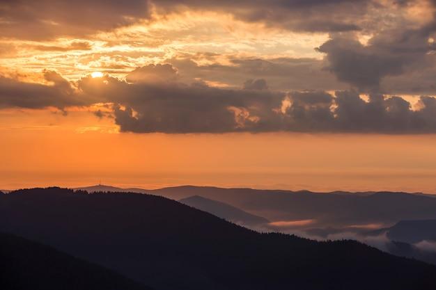 Szeroka panorama mglistych gór o zachodzie słońca na jasnym jasnym niebie pomarańczowy.